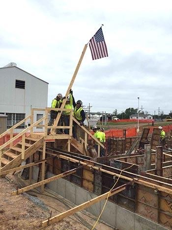 Lindblad Construction workers hoisting up United States flag